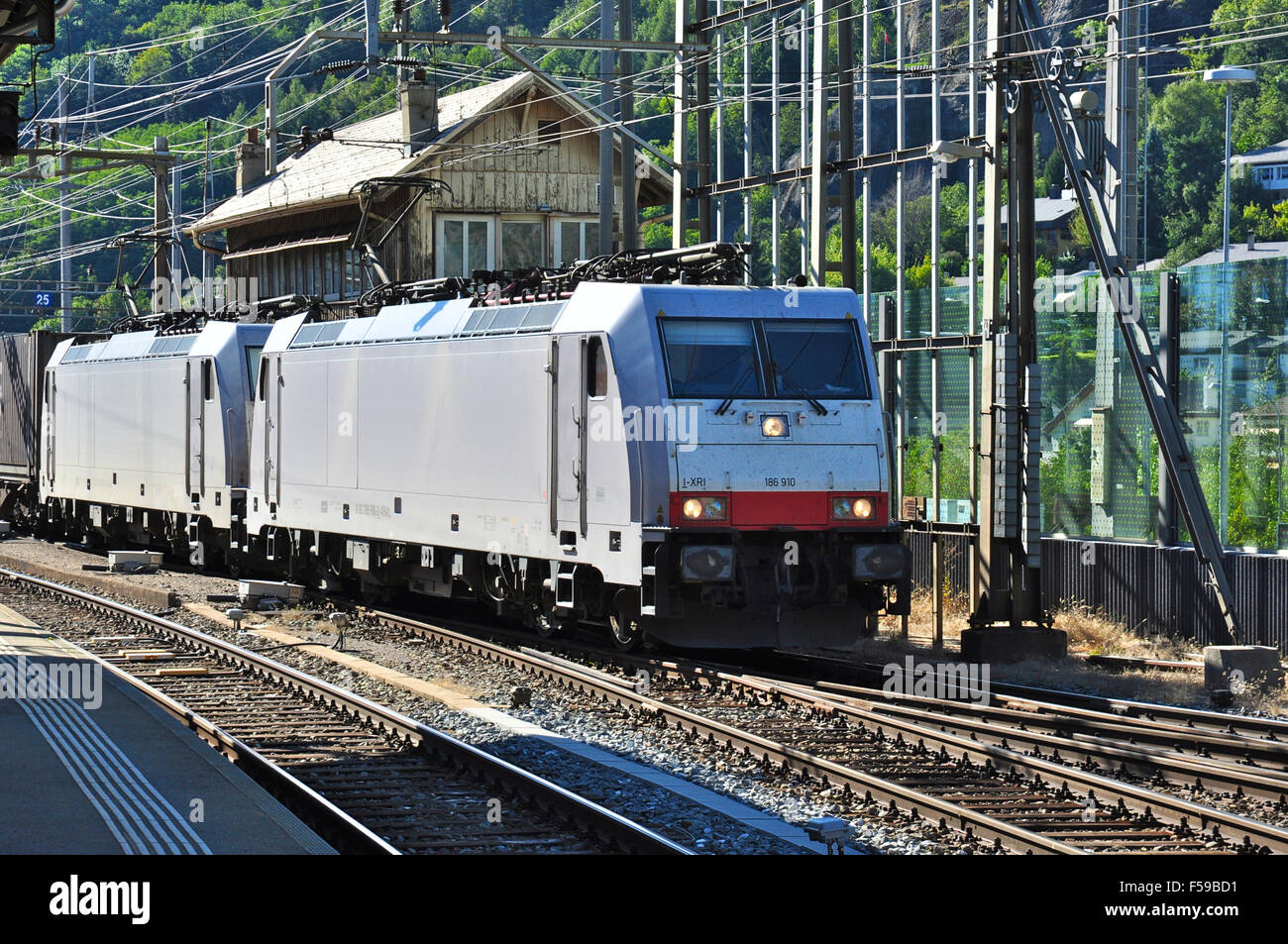Class 186 electric locomotives double head a freight through Brig station headed by 186910, Brig, Valais, Switzerland Stock Photo