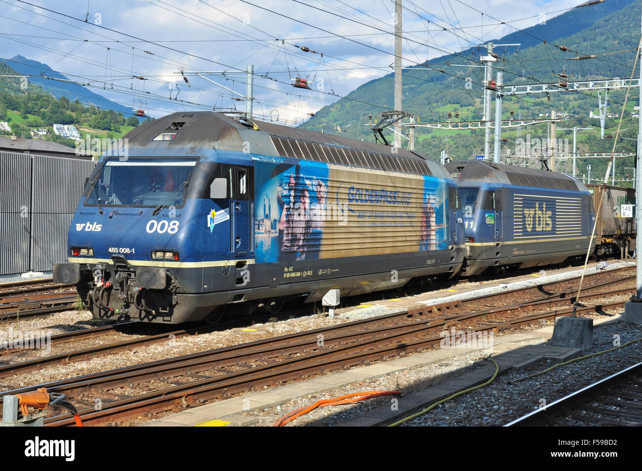 Class Re 465 electric locomotives double head a freight through Brig station headed by 465008, Brig, Valais, Switzerland Stock Photo