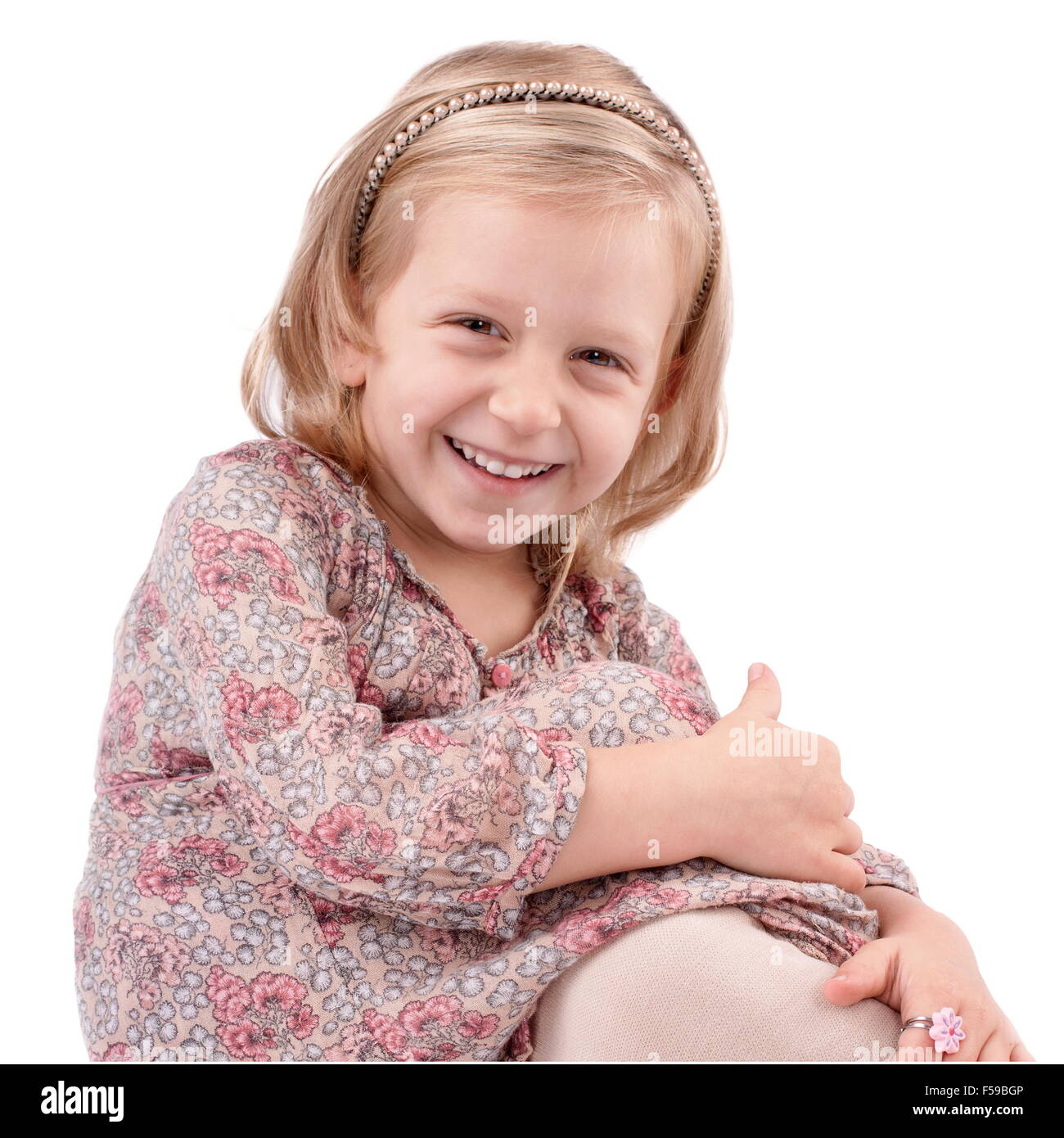 Cute little girl dressed in floral, dress having fun - Stock Image