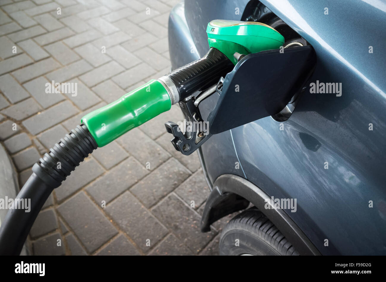 Filling modern dark blue car with petrol at an automatic gas station - Stock Image