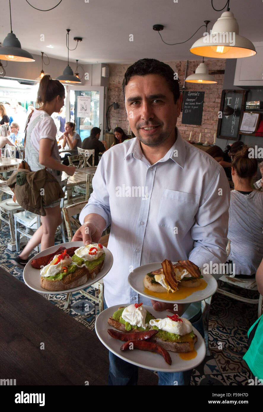 Broadway Market, London E8: El Ganso Spanish tapas restaurant: the manager Ihsan Tuncay with some breakfast dishes - Stock Image