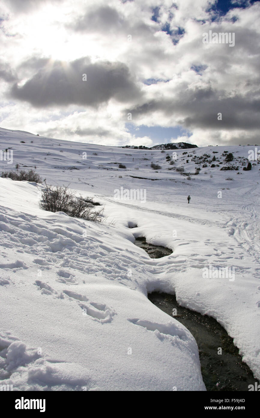 Hicker walking by river wading through the snowy landscape,  province of Lleida, in the autonomous community of - Stock Image
