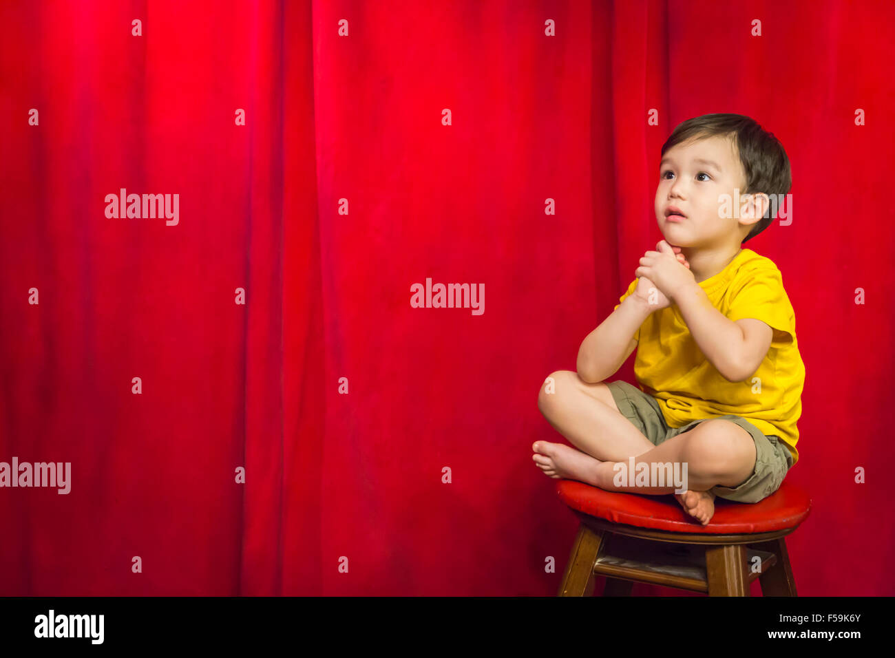 Handsome Mixed Race Boy Sitting on Stool in Front of Red Curtain. - Stock Image