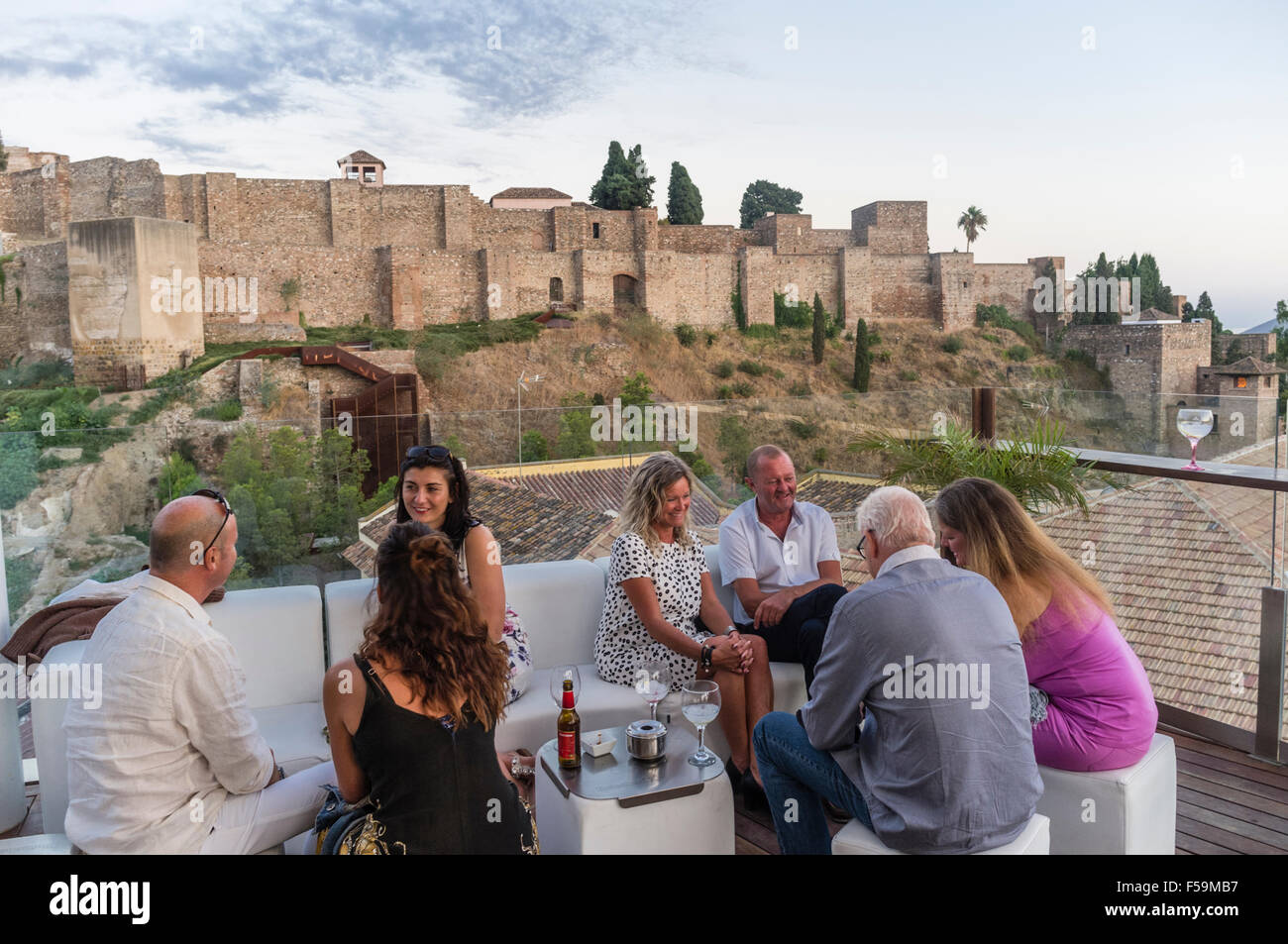 People with Alcazaba castle in background at the rooftop lounge bar of  Alcazaba Premium Hostel, Malaga, Andalusia, - Stock Image