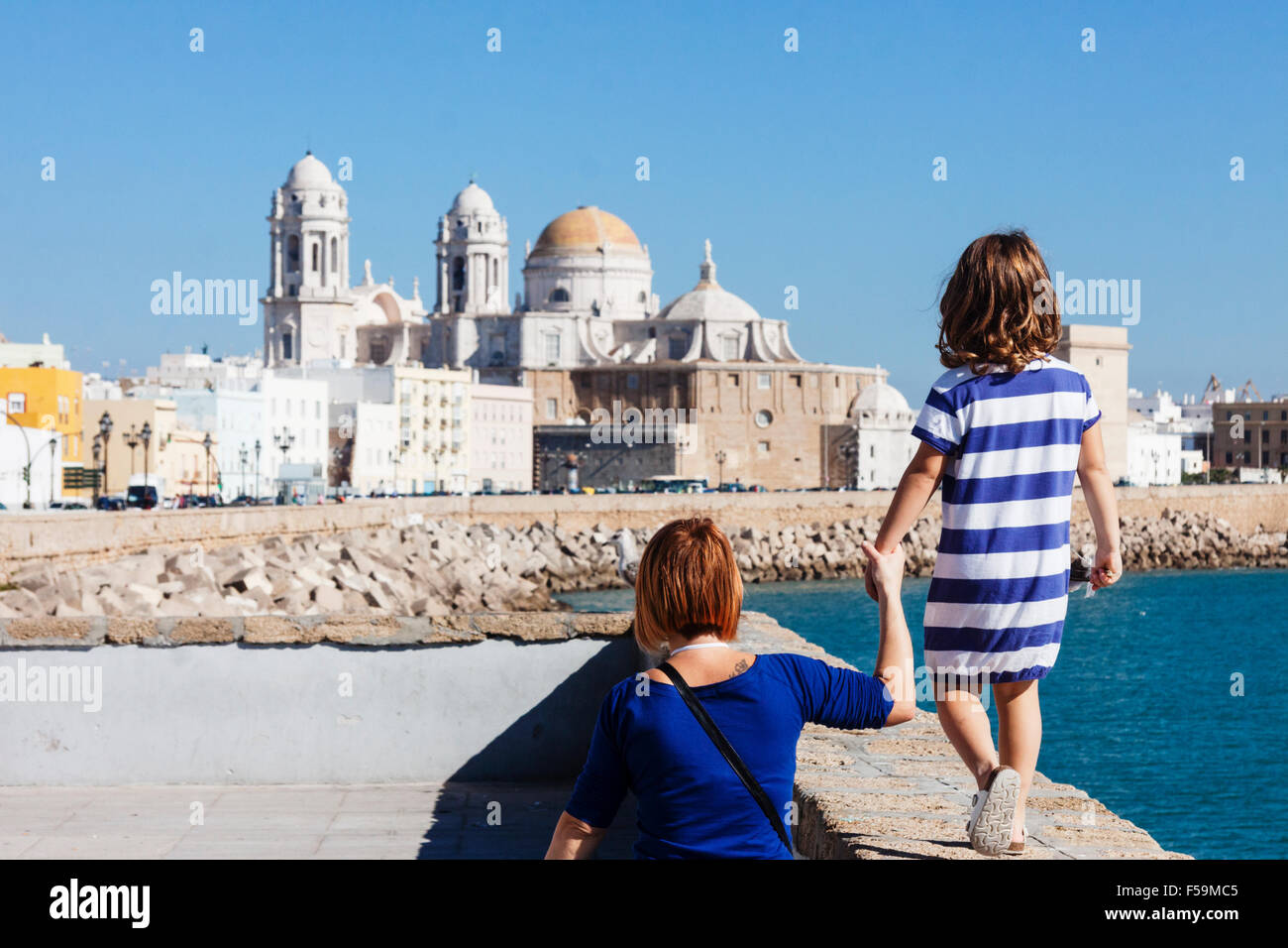 Tourists mother and daughter with blue striped t shirt on the promenade with the Cathedral of Cadiz, Andalusia, - Stock Image