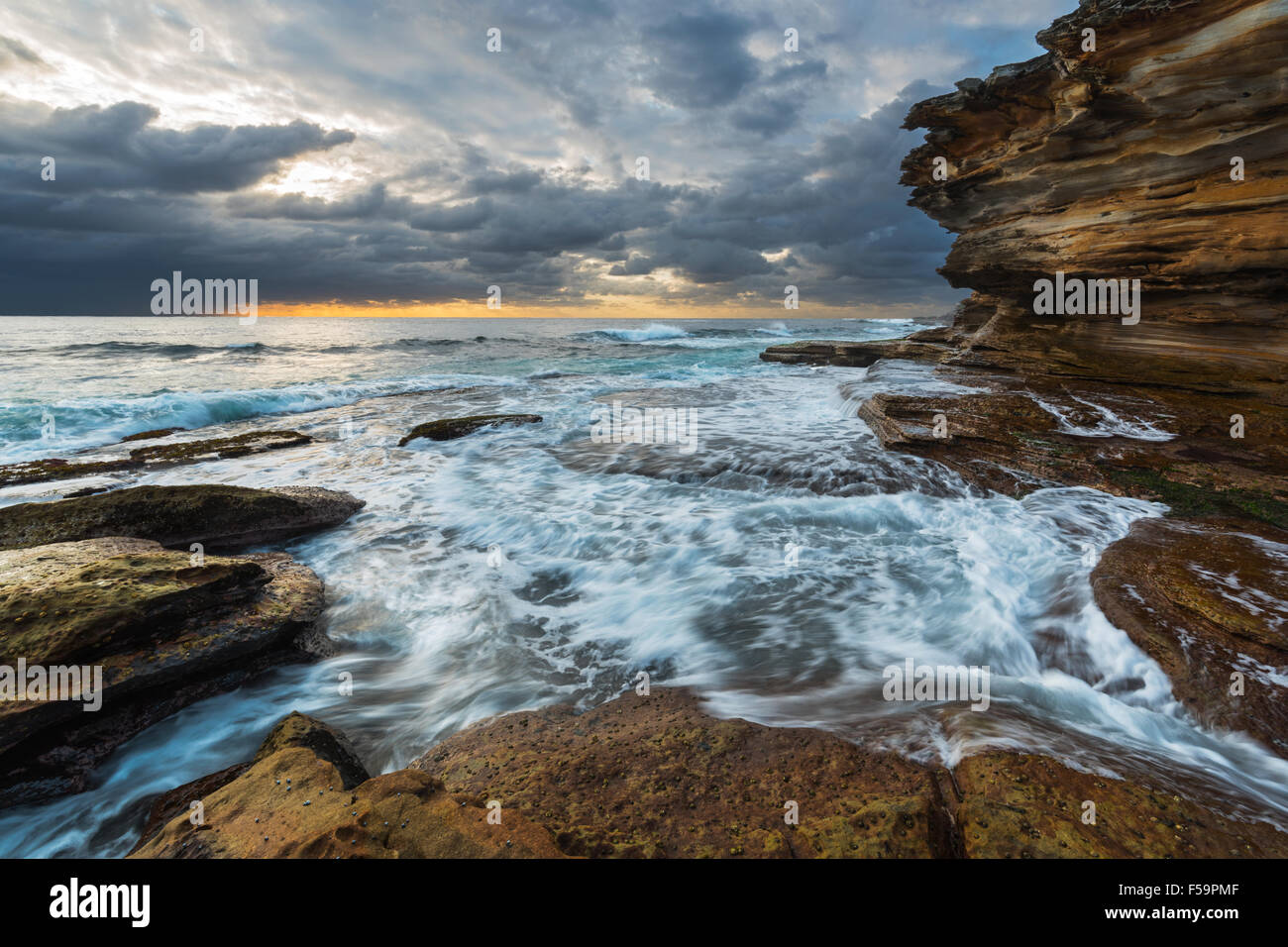 Seascape sunrise with unrest sea and grim sky and cliffs - Stock Image