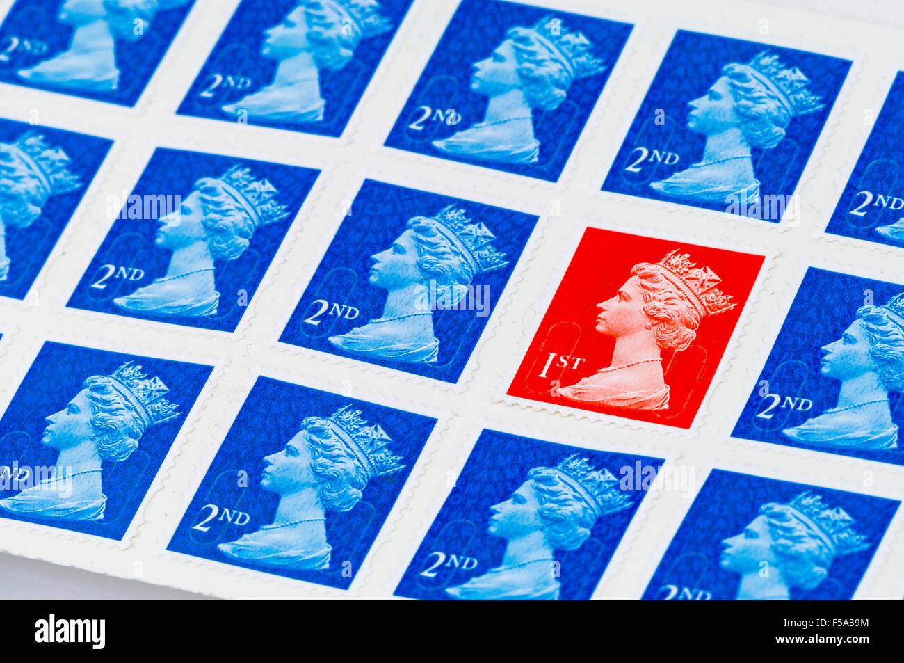 A first 1st class Royal Mail stamp among second 2nd class stamps - Stock Image