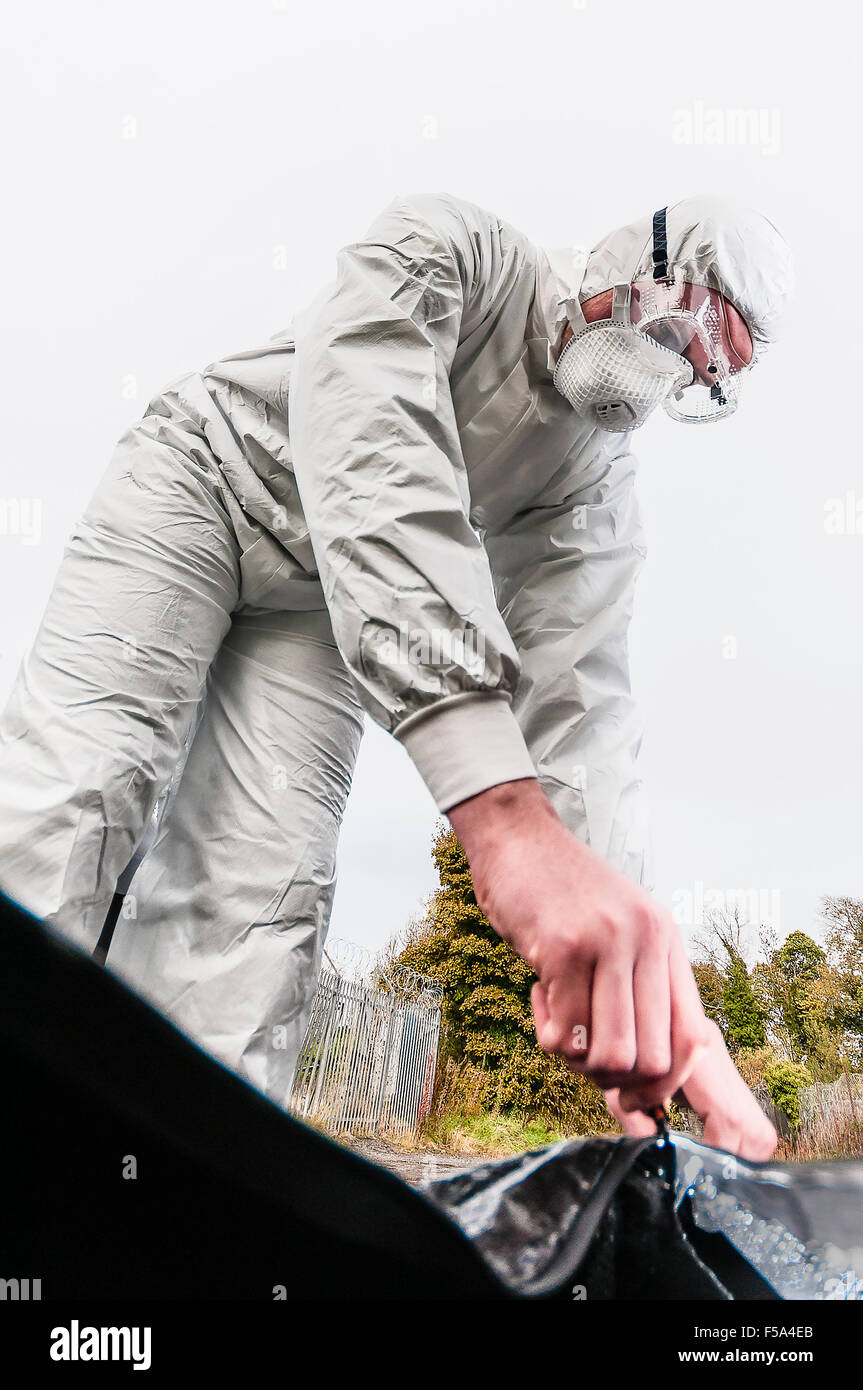 A Scene of Crime Officer (SOCO) wearing protective mask and goggles zips up a body bag (point of view from inside - Stock Image