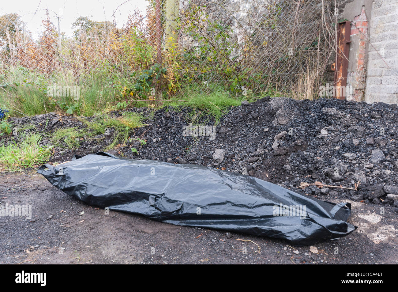 A body inside a body bag at an isolated location. - Stock Image