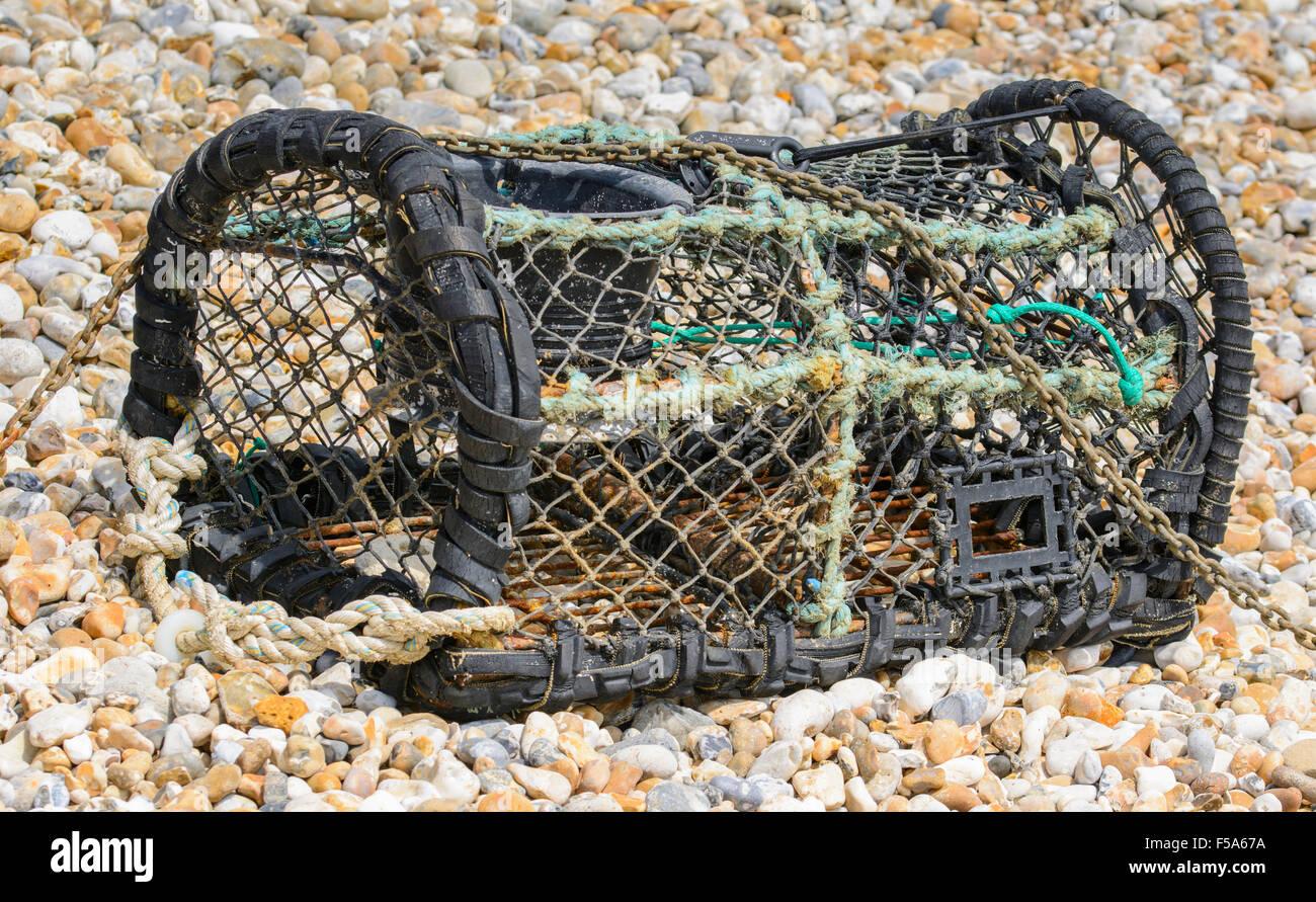 Lobster pot / Fish basket on a shingle beach. - Stock Image