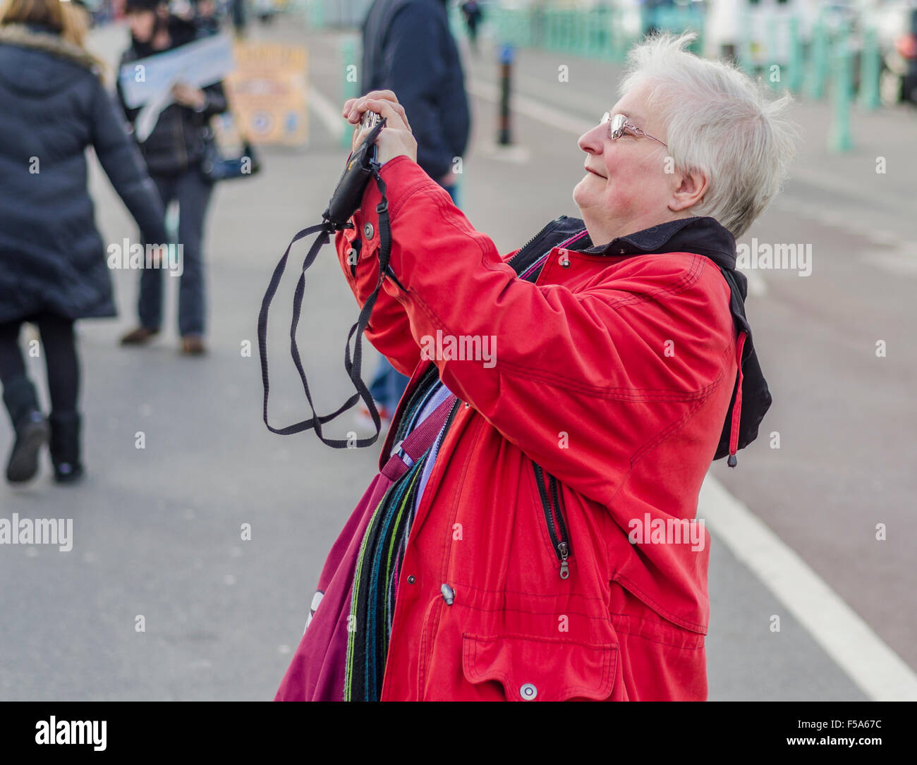 Senior lady taking photos with a compact camera. - Stock Image