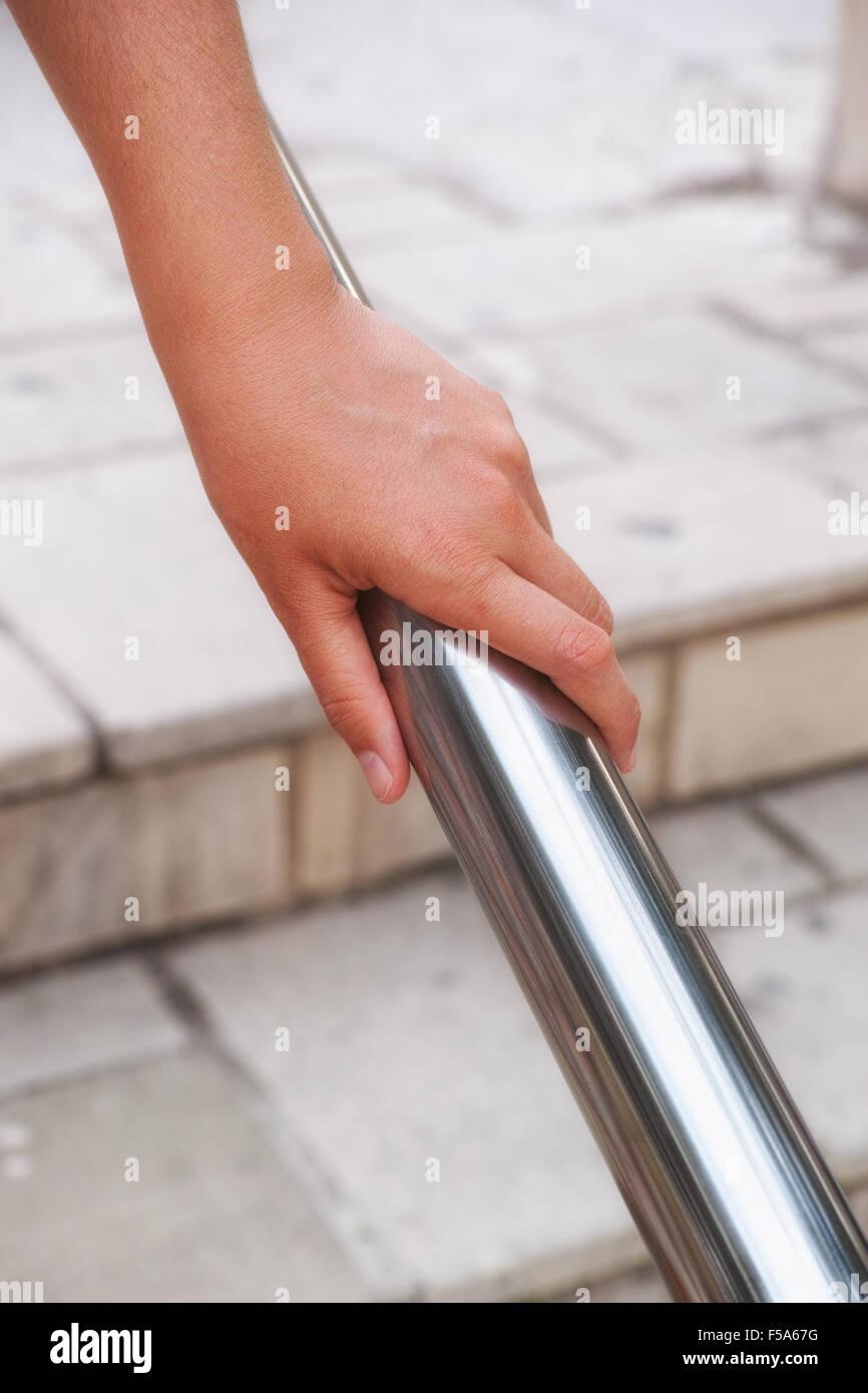 Woman hand using a handrail. Urban scene. - Stock Image