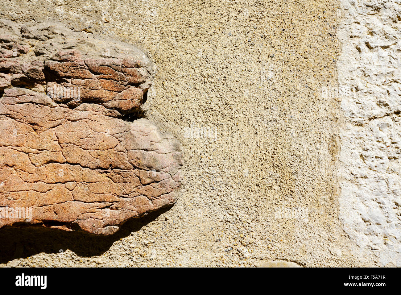 Old wall and protruding rock - Stock Image