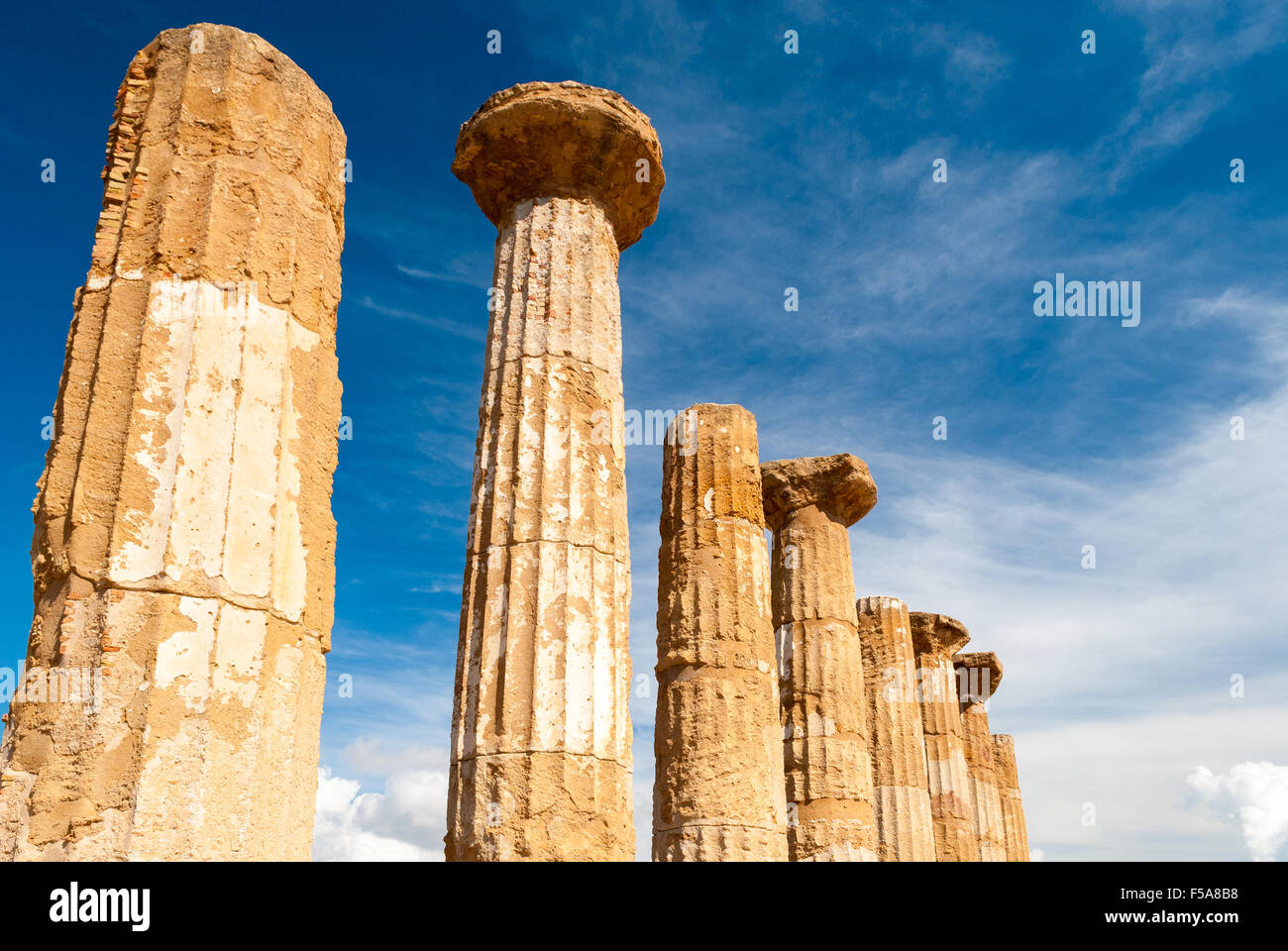 Doric columns of the Heracles temple in Agrigento with blue sky and clouds in background - Stock Image