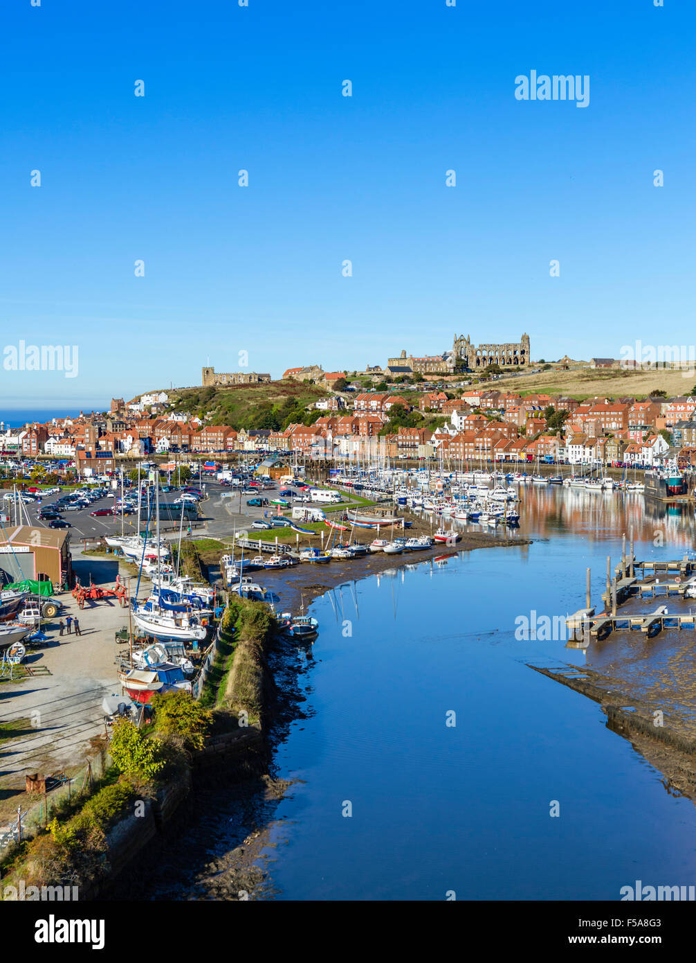 View over the fishing port of Whitby with the Abbey on the hilltop, North Yorkshire, England, UK - Stock Image