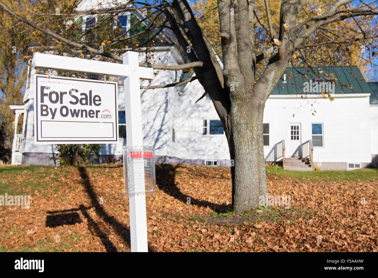 House for sale with real estate sign in front yard. For sale by owner. - Stock Image
