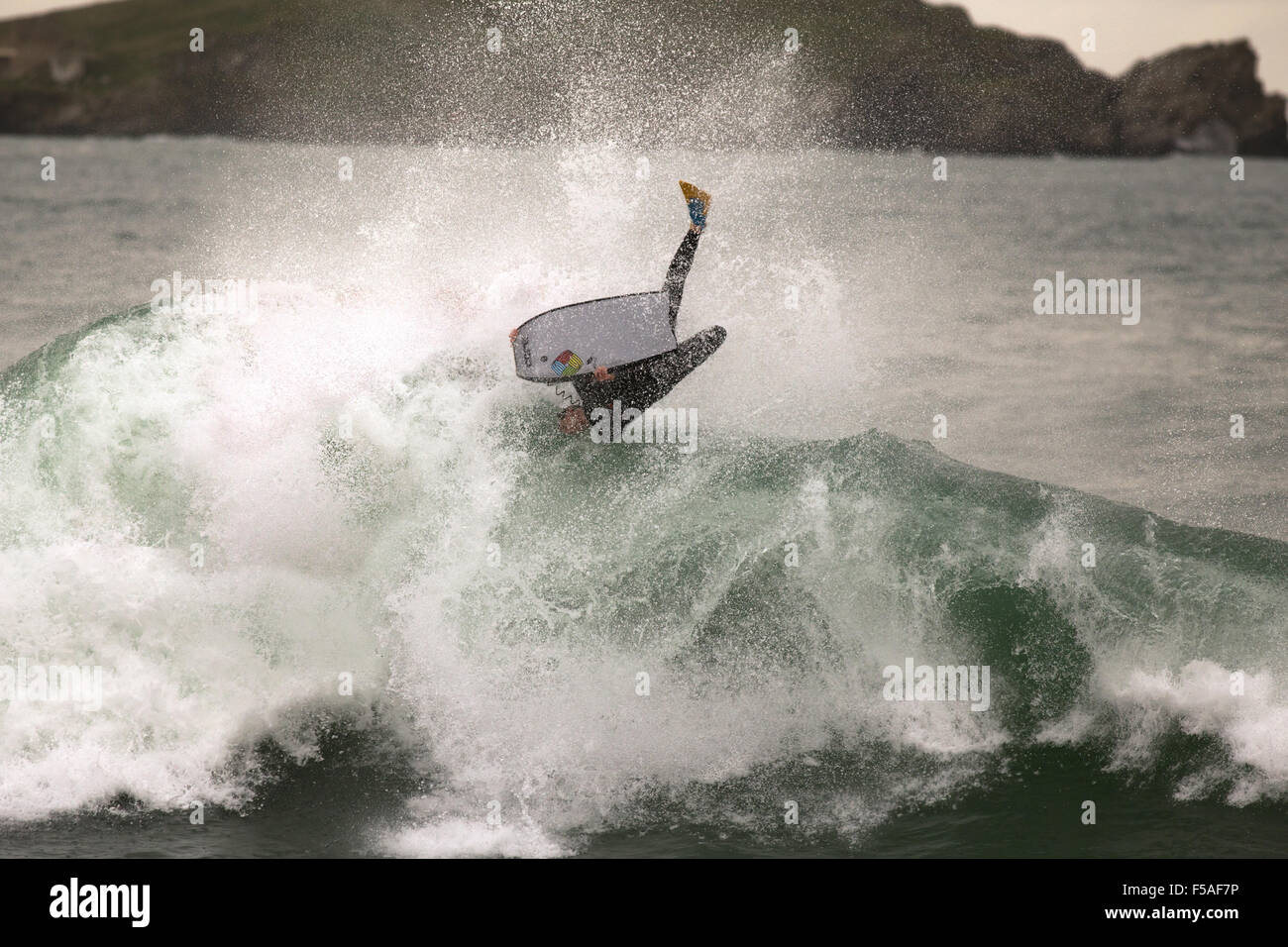 A bodyboarder is flung into the air at the top of a wave - Stock Image