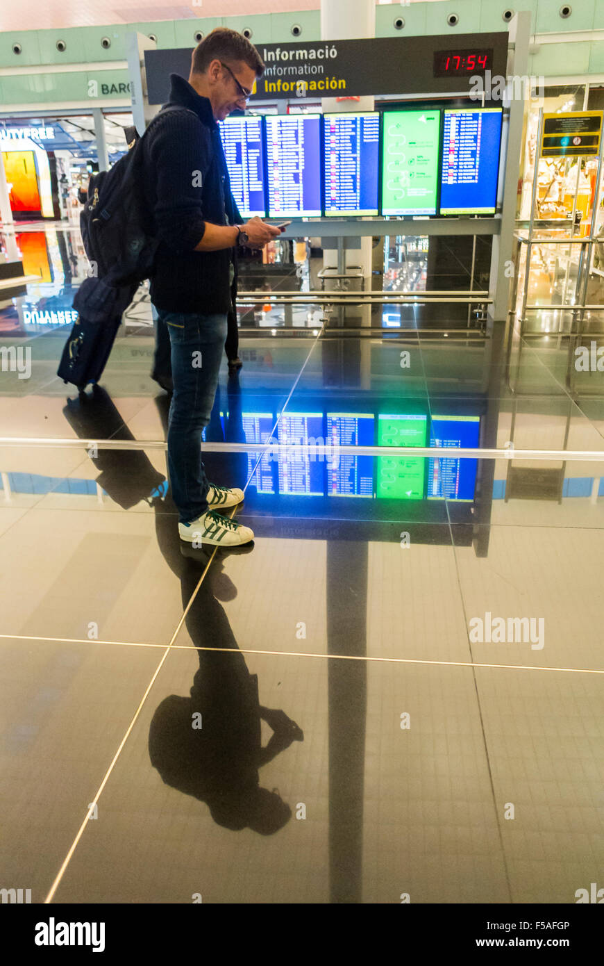 "Barcelona, Spain, Airport ""El Prat"", Terminal 1, Scenes, Man Looking at Smart Phone in Hallway, Departures Sign, Stock Photo"