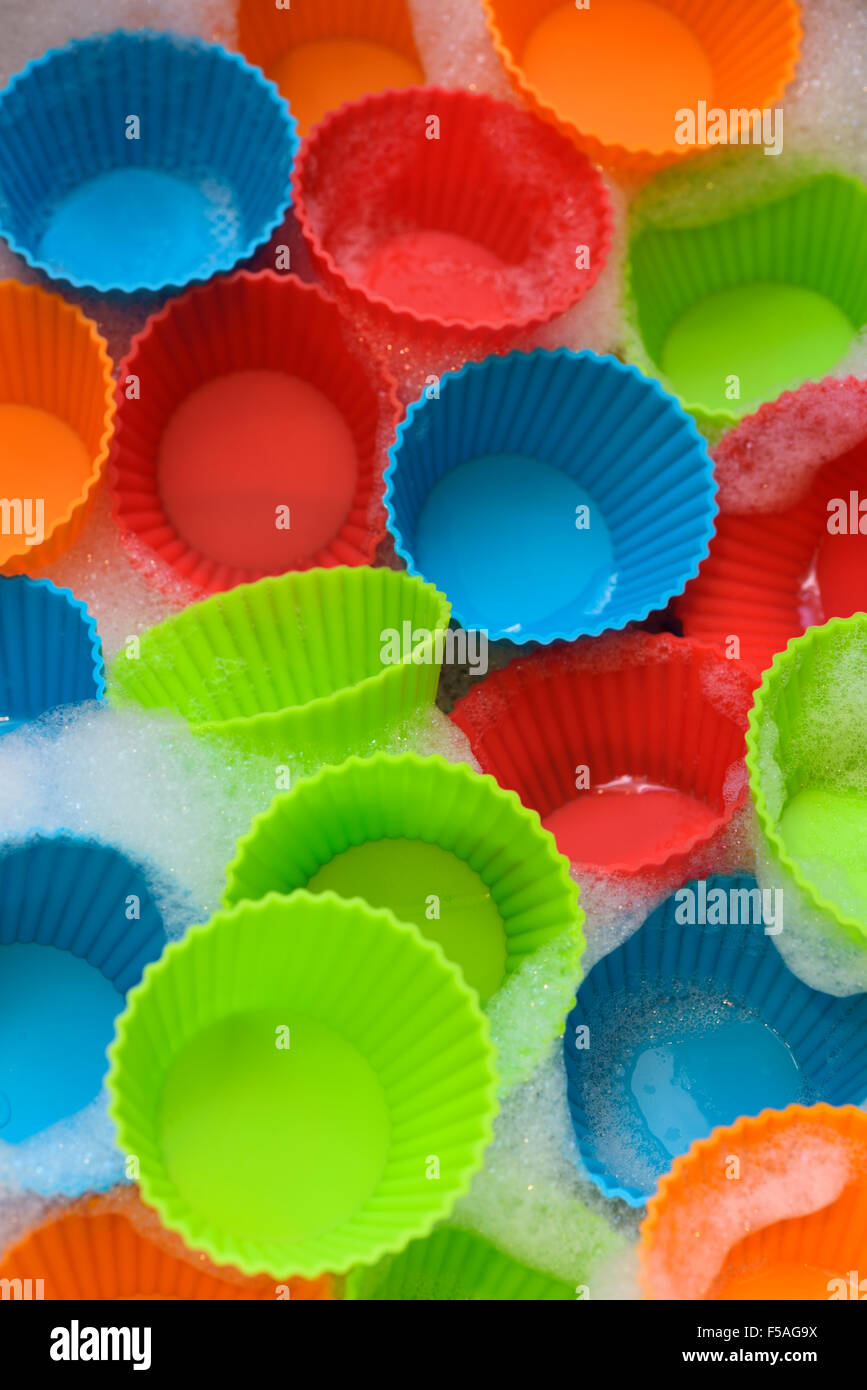 Colorful silicone plastic cups for making cupcakes in water with suds - Stock Image