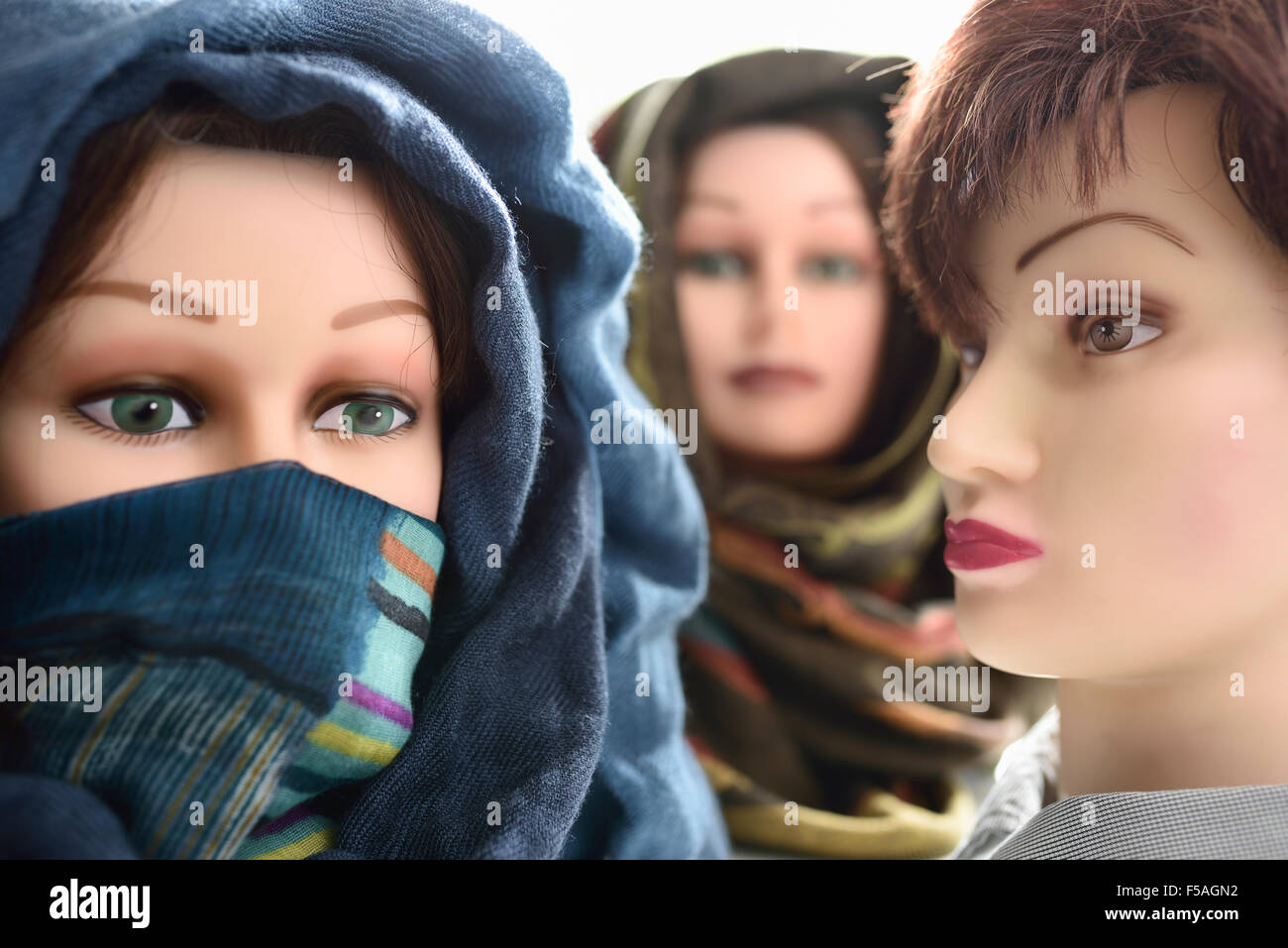 Two mannequin heads in hijabs and one without - Stock Image