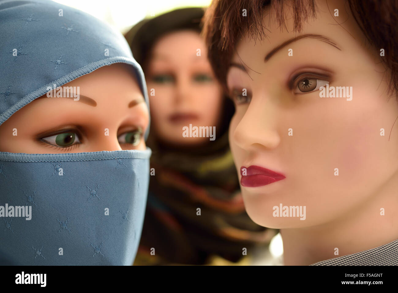 Female mannequin heads in hijab and niqab and one without - Stock Image