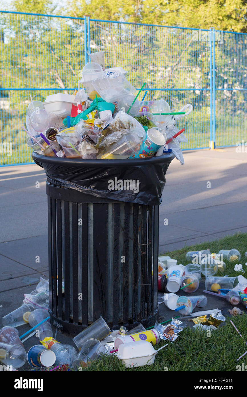 Trash bin overflowing with recyclables and food containers. - Stock Image