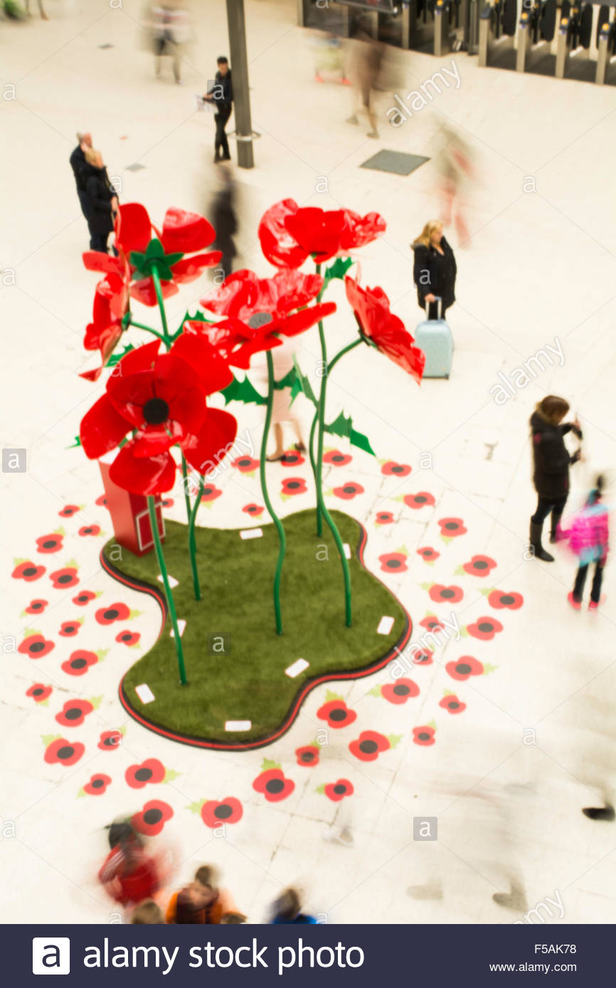 People swirling past a giant poppy installation on the concourse of Waterloo Station as part of London Poppy Day - Stock Image