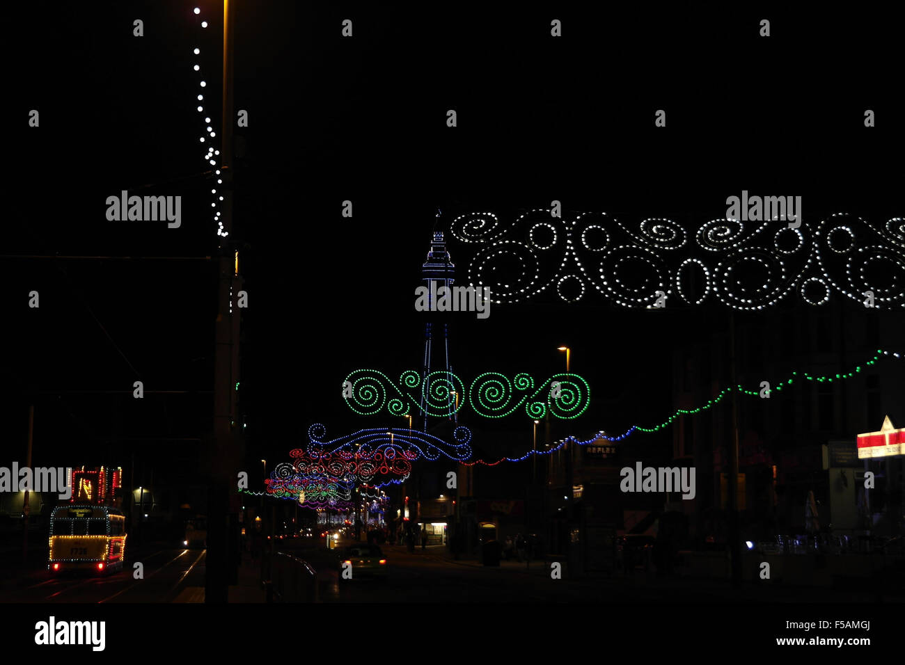 Night view, north to Tower, colourful Scrolls across Central Promenade by tramway with Frigate Tram, Blackpool Illuminations, Stock Photo