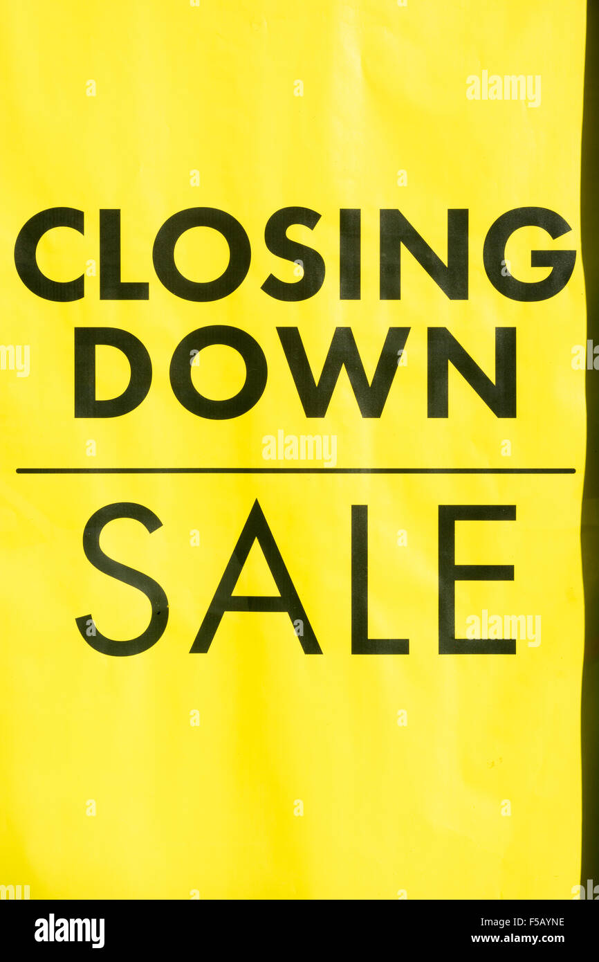 Death of the High Street metaphor / concept. Yellow closing down sign in shop window. Metaphor high street recession, Stock Photo