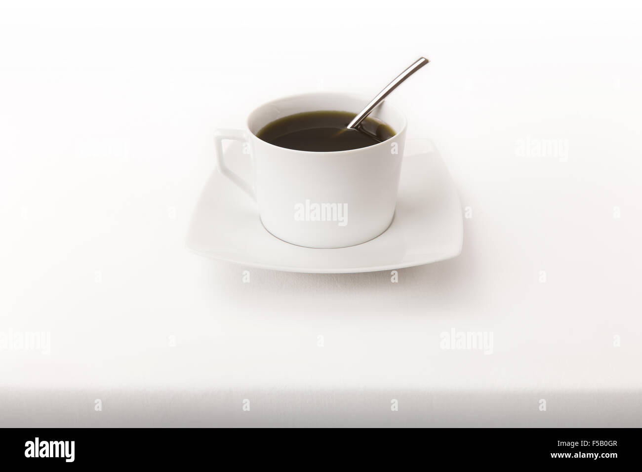 A modern cup of tea with a spoon on a white tablecloth with real shadow bottom - Stock Image
