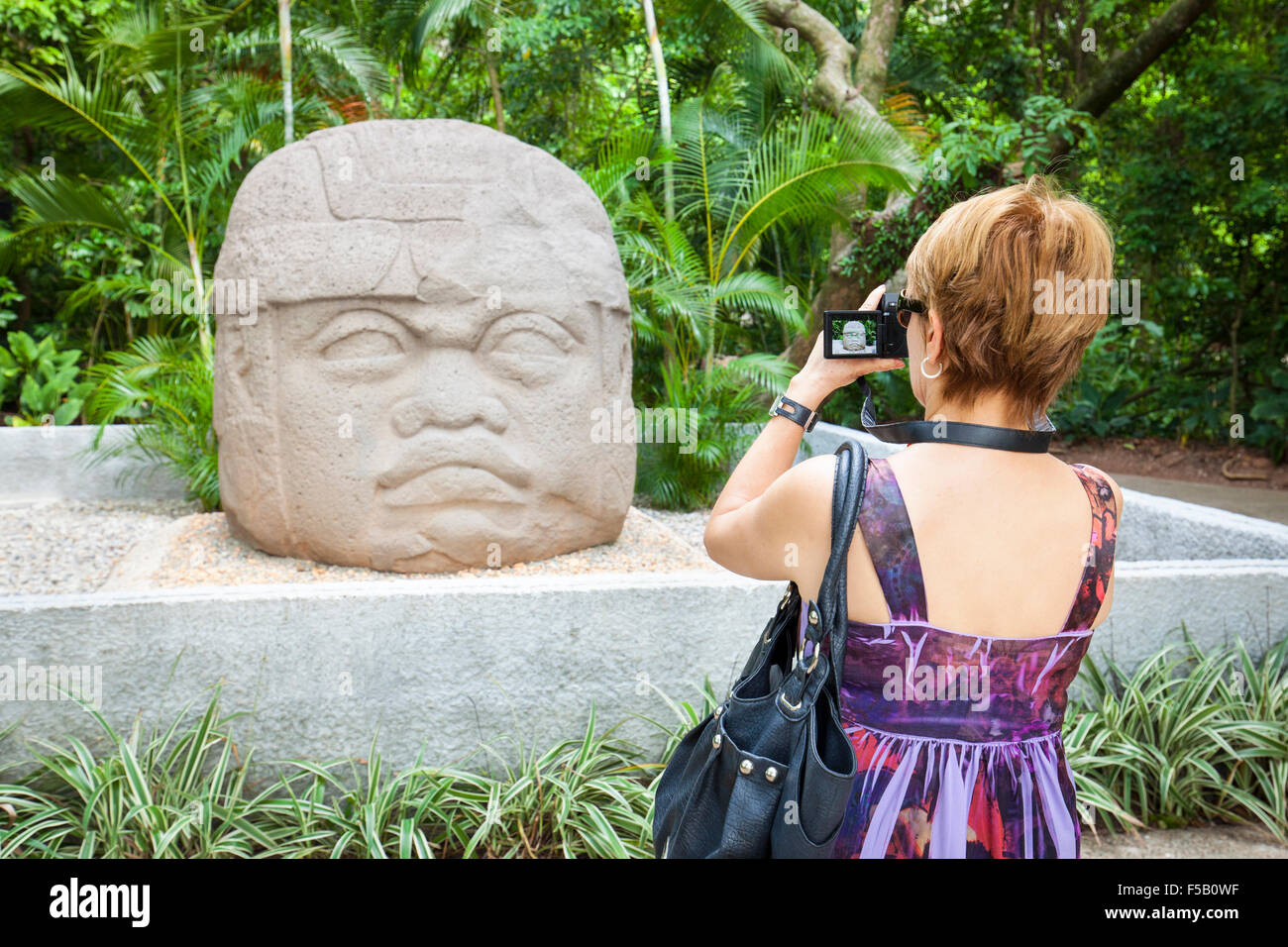 Female tourist photographs the Olmec stone carving Colossal Head in La Venta park, Villahermosa, Tabasco, Mexico. - Stock Image