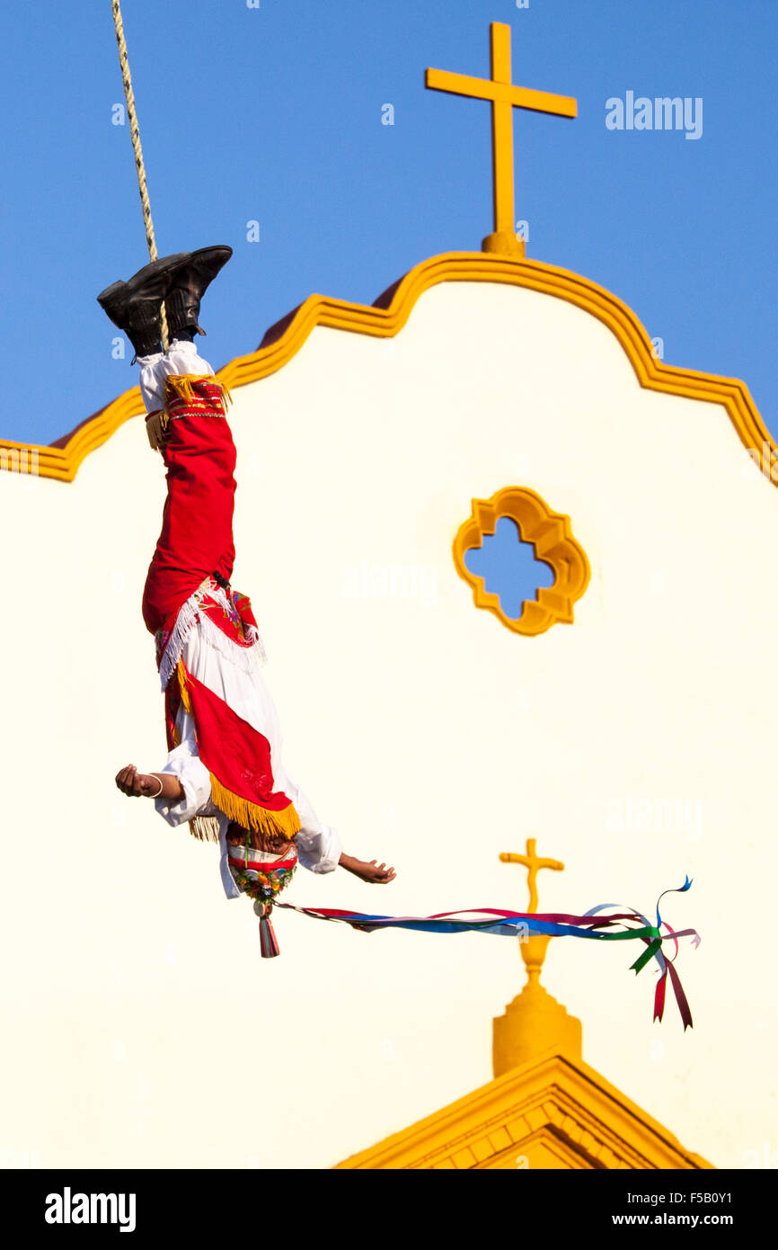 A serene volador or flyer swings in front of a church during an Totonac ritual performed  in Papantla, Veracruz, - Stock Image