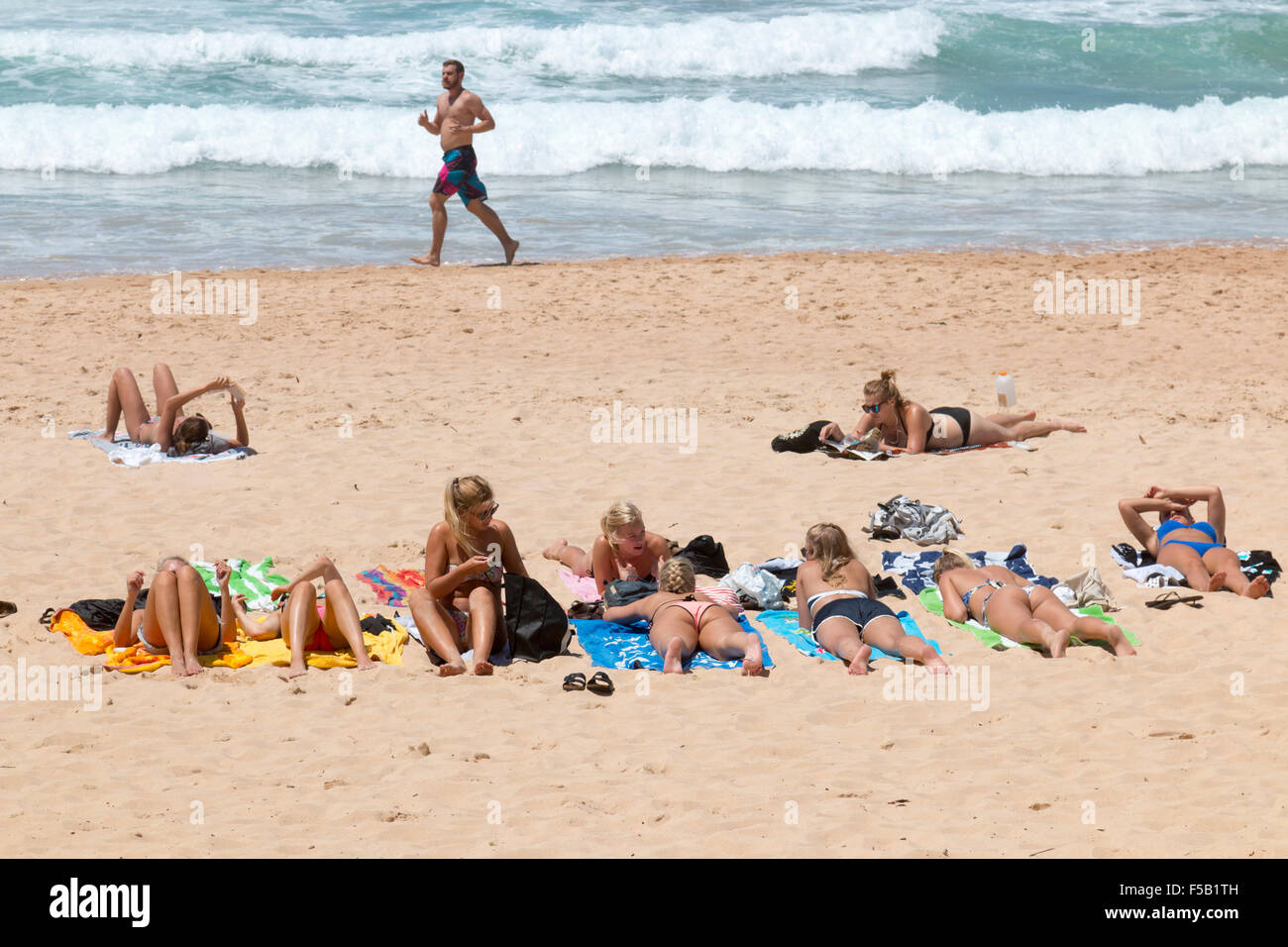 teenage girls sunbathing on Manly Beach Sydney, Australia - Stock Image