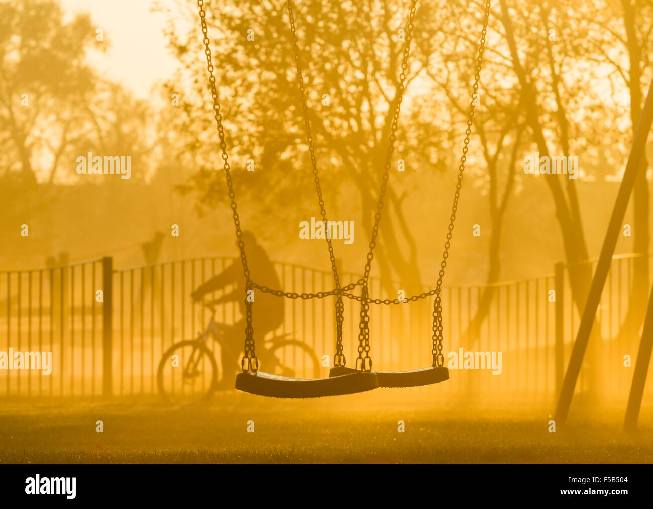 A mature male cycles past swings in public park. UK - Stock Image