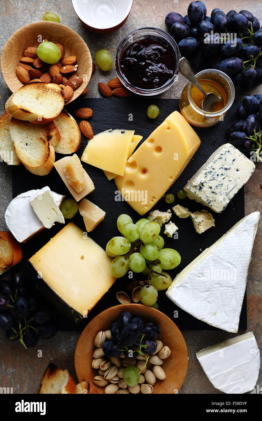 various cheeses and grapes on slate - Stock Image