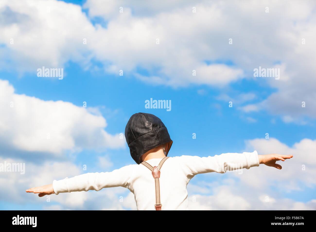 Little boy in vintage clothes dreams of flying with