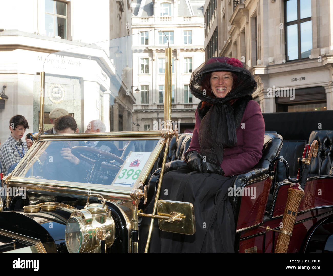 A smiling lady in period costume sits in a 1904 De Dion Bouton, during ther Regents Street Motor Show - Stock Image