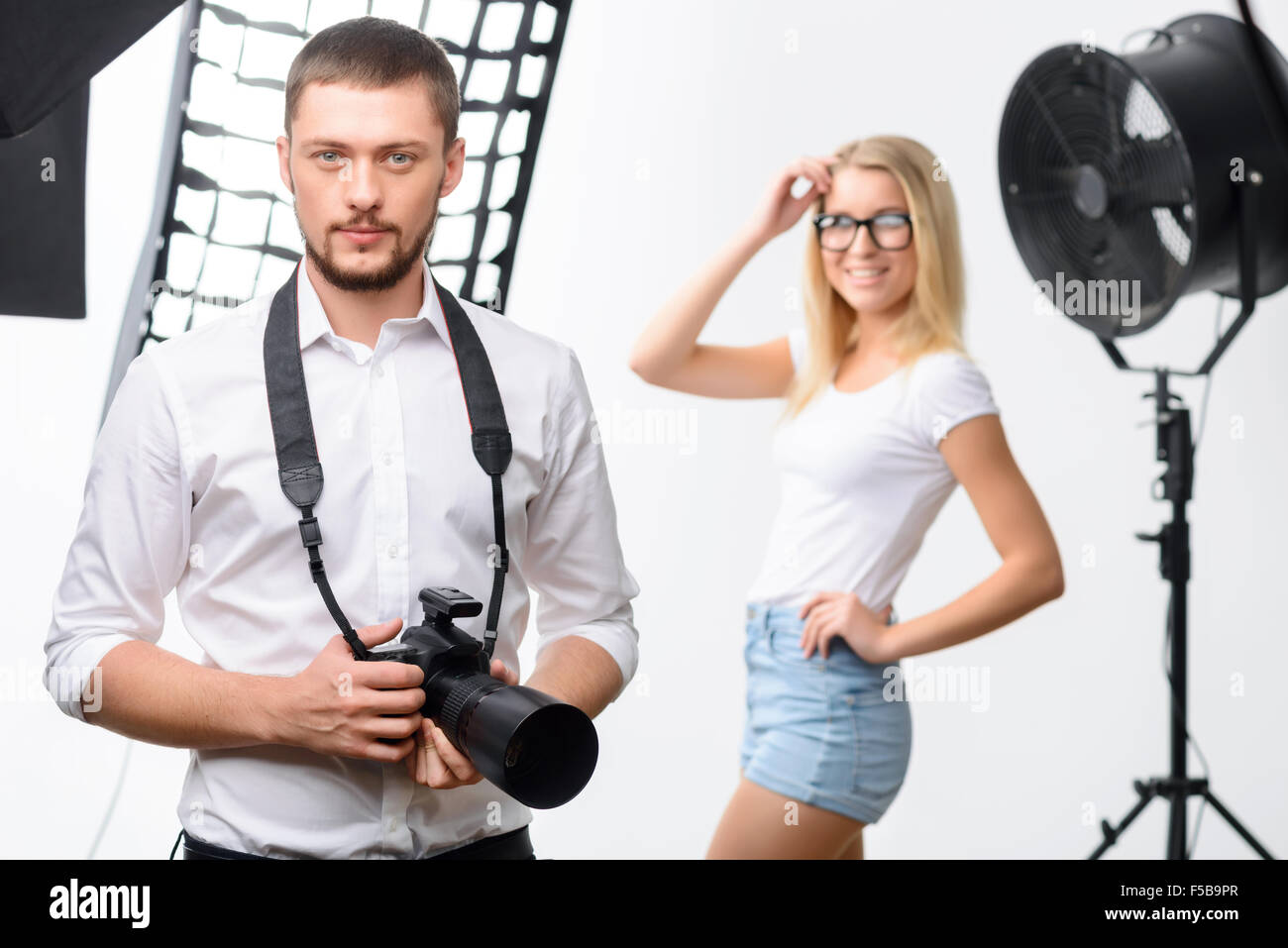 Male young photographer holding a camera - Stock Image