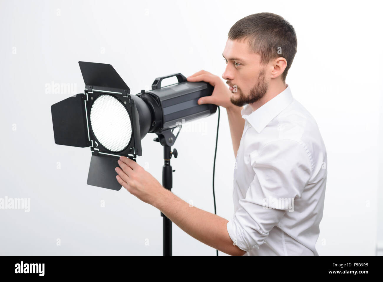 Young male professional photographer is busy fixing the spotlight. - Stock Image