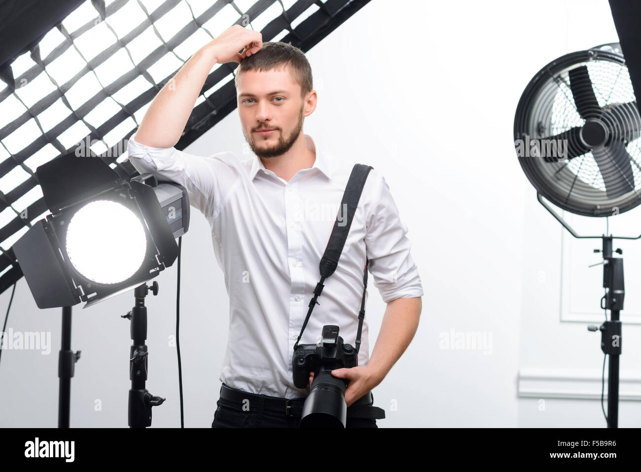 Young male photographer leans on the spotlight - Stock Image