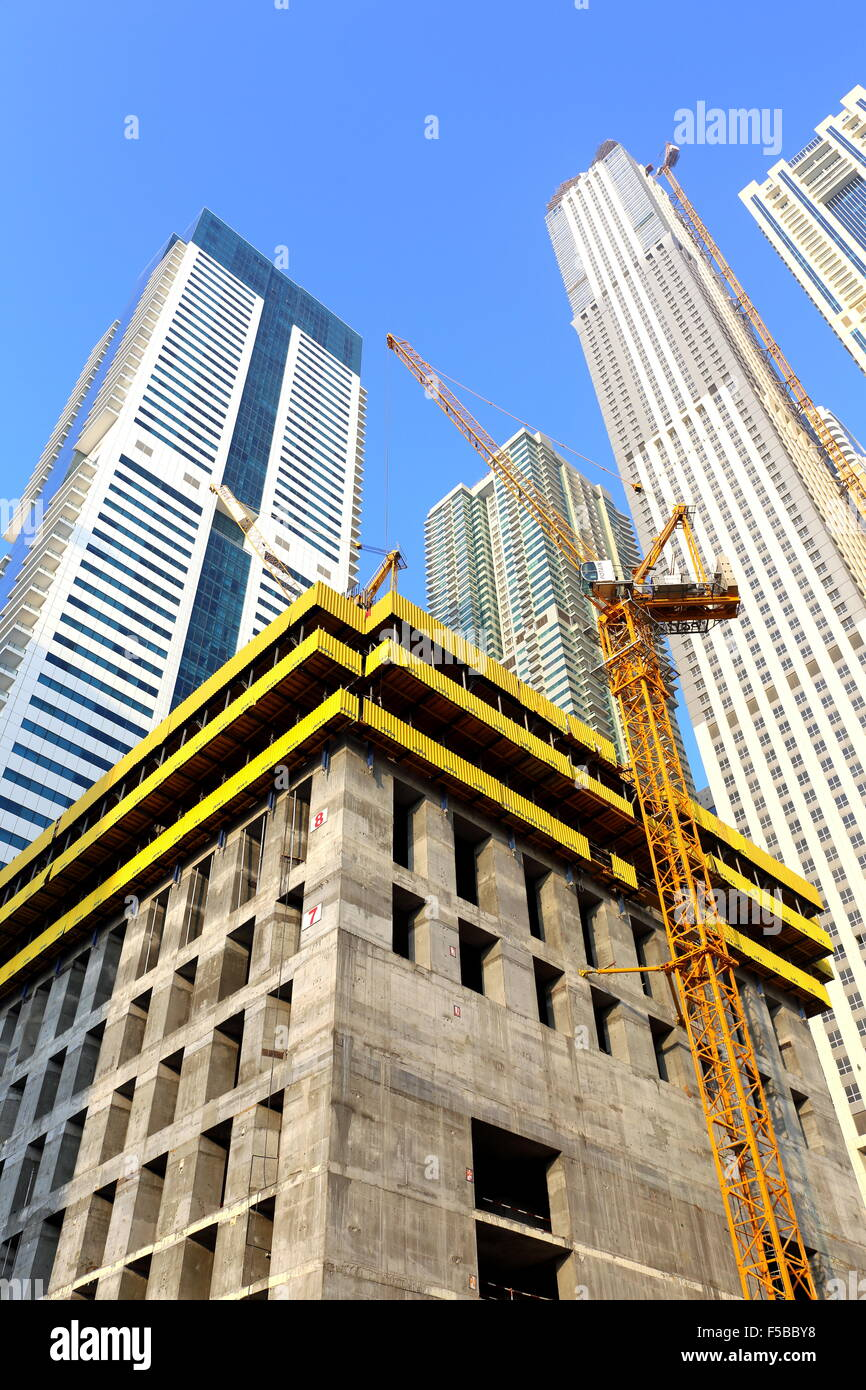Construction work going on with residential apartments behind at Media City, Dubai, United Arab Emirates - Stock Image