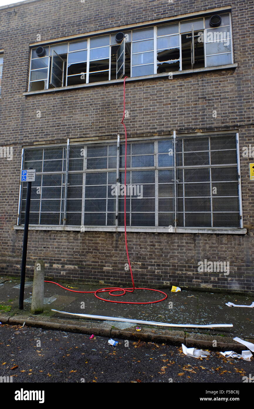Broken windows at the rave location and hose from fire extinguisher hanging out of the window where people tried - Stock Image