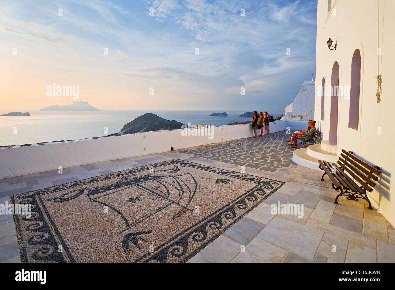 People sitting on a bench in Plaka village on Milos island, Greece - Stock Image