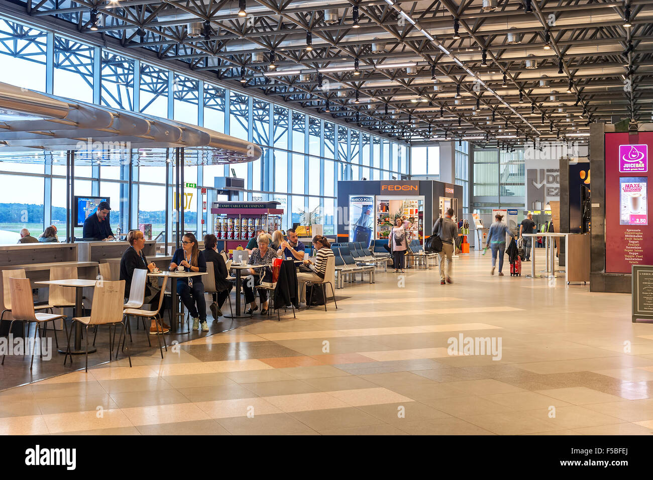 People sitting in café and walking inside Terminal 2 of ...