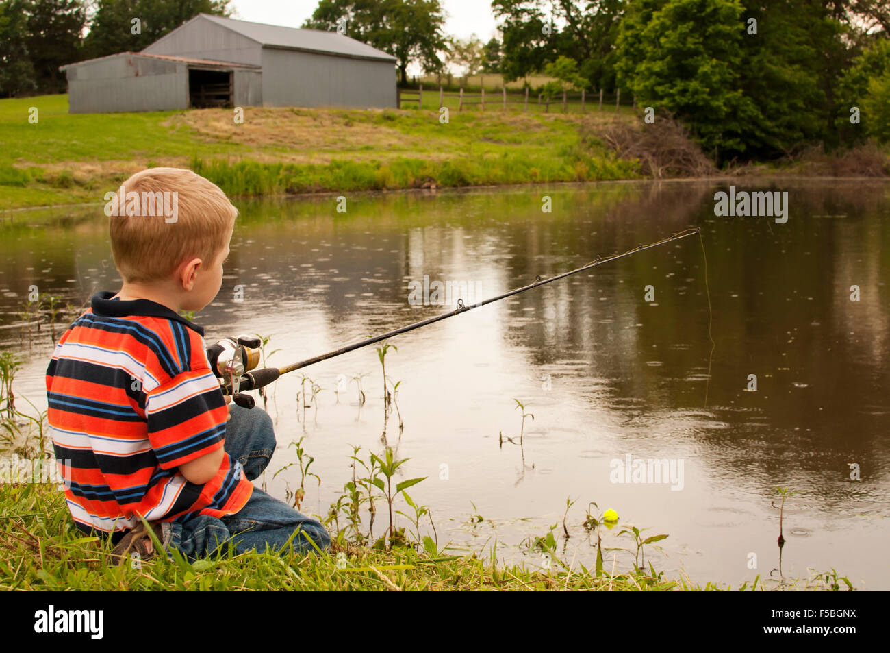 Young boy fishing in pond. - Stock Image