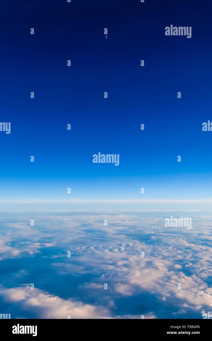 Clouds shot from above, as seen from an airplane window. The moon is visible too. - Stock Image