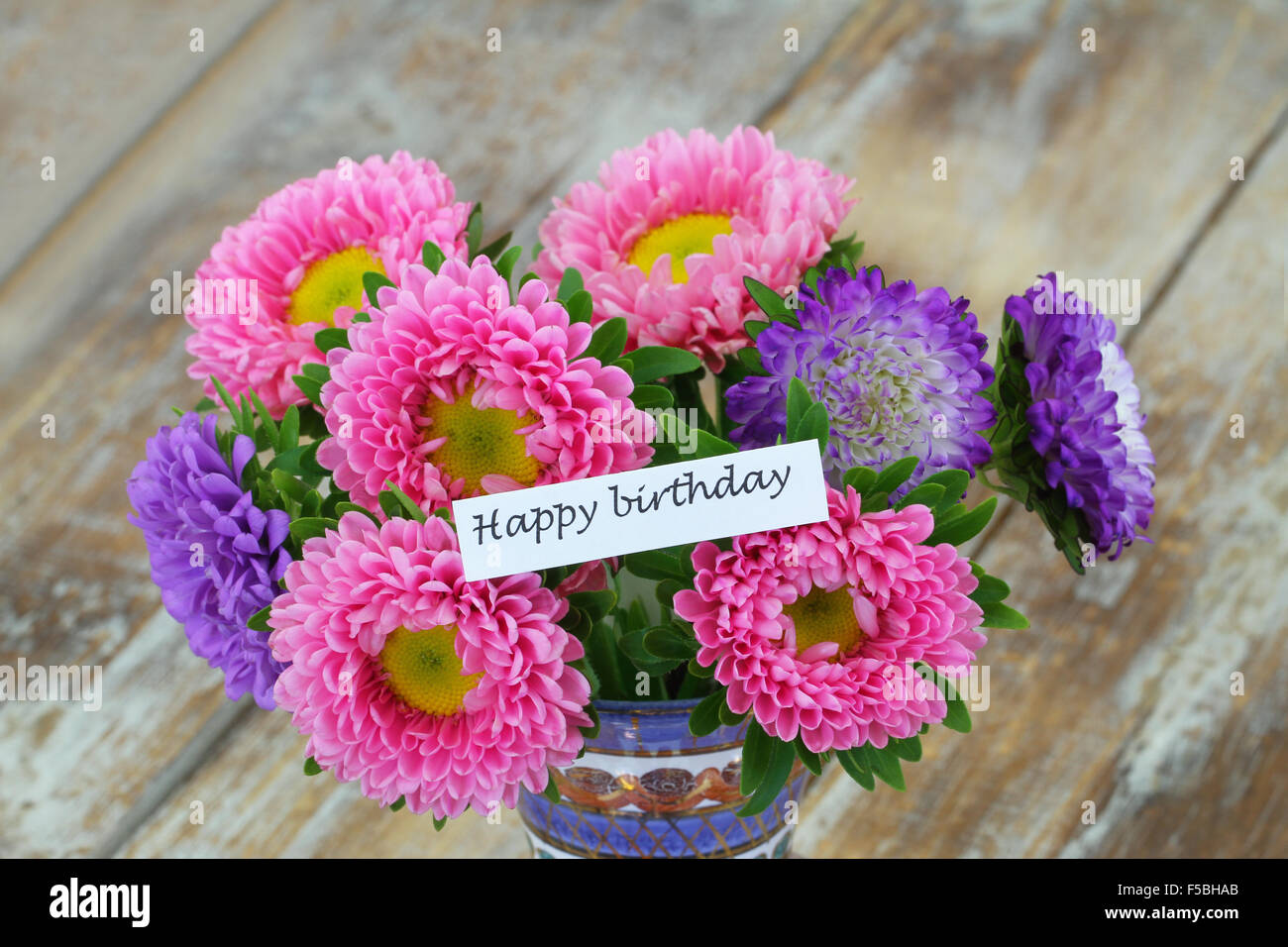 happy birthday card with colorful aster flower bouquet on rustic wooden surface
