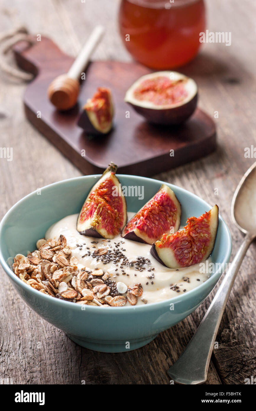 Breakfast with muesli, yogurt, figs and chia seeds in a blue bowl on a wooden background - Stock Image