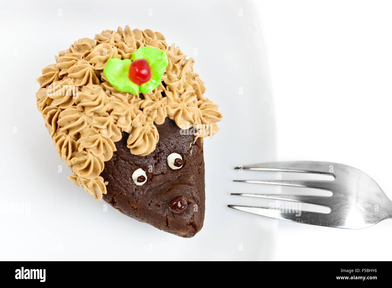 Chocolate cake decorated as hedgehog on white dish isolated Stock Photo