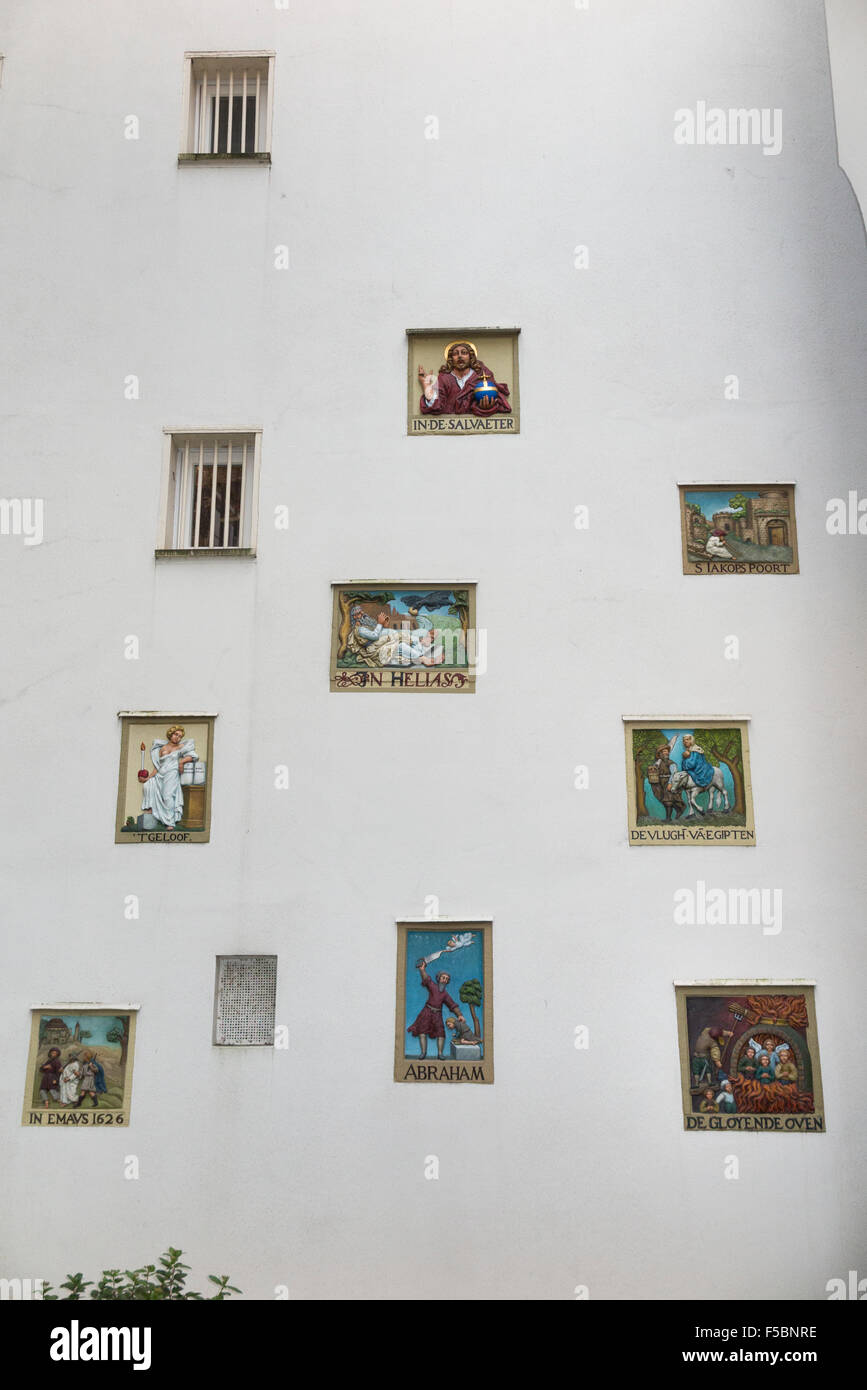 Religious plaques / paintings / depictions of the saints and other Biblical scenes on the wall / walls of the Begijnhof Stock Photo